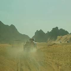 Pick up truck pulling carrier on desert. Stock Footage