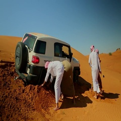 Arab friends removing sand beneath a bogged FJ cruiser on desert. Stock Footage