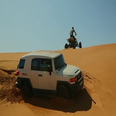 Arab man drifting quad bike on desert, bogged FJ cruiser in the foreground. Stock Footage