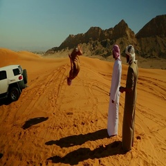 Friends with Arab man doing somersault on desert. Stock Footage