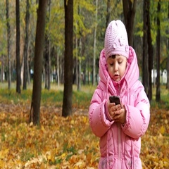 Kid talking on the phone in the park Stock Footage