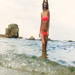 Beautiful young model wearing red swimming suit, posing on the beach Stock Footage