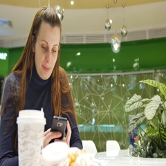 One young white woman uses phone in a cafe in the supermarket a public place Stock Footage