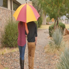 Young millenial couple walk away under bright umbrella in rain Stock Footage