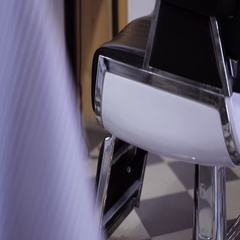 A man sits down on a barber chair in a barbershop Stock Footage