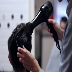 Barber dries hair for male client with the hairdryer and comb, close-up. Stock Footage