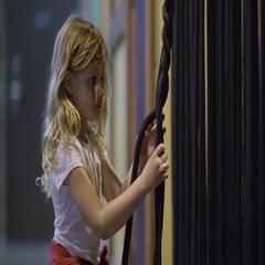 Little Girl Practices Braiding Technique On Rope, She Concentrates Stock Footage