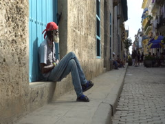 Elderly Afro-American man with gray-haired beard in red bandanna is sitting on Stock Footage