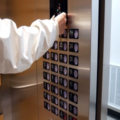 Woman scanning key tag and pressing a button the ten floor in an elevator Stock Footage