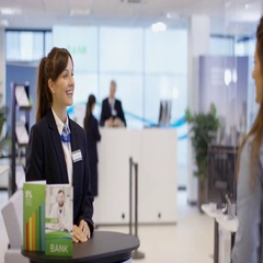 4K Customer waits to meet with financial adviser in modern bank Stock Footage