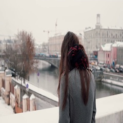 Back view. The sad brunette girl standing on the bridge sighs and looks at the Stock Footage