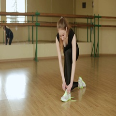 Beautiful girl tying running shoes.  Young girl tying Shoe laces in the gym. Stock Footage