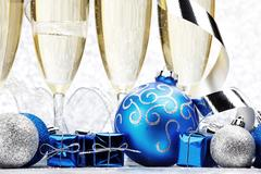 Glasses of champagne and decorative christmas balls on glitter background Stock Photos
