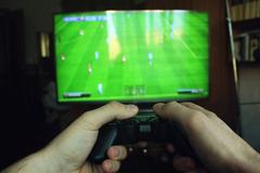 Playing football with the joystick on the game console Kuvituskuvat