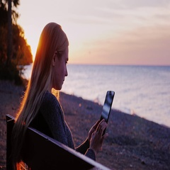 Young woman with long hair sitting on a park bench. Uses tablet. At sunset seen Stock Footage