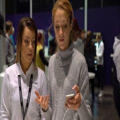 Shop assistant helps a young woman to choose a new phone in an electronics store Stock Footage