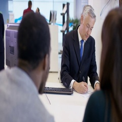 4K Modern city bank, adviser assisting couple & getting signature on document Stock Footage