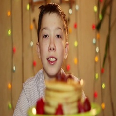 American pancakes. The boy looks at the pancakes with strawberry jam. Stock Footage