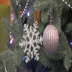 Little girl decorating Christmas tree, silver star, ball, winter Stock Footage