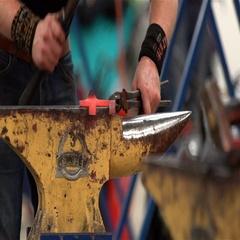 Some blacksmiths forge horseshoes. Slow motion. Stock Footage