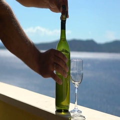 Male hands open bottle of white wine on the balcony near the sea on vacation Stock Footage