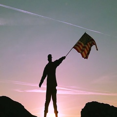 Soldier waves American Flag Against Sunrise Sky. Slow Motion  Stock Footage