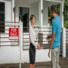 """Female realtor meets a young man near the new house and sign """"For Sale"""". Stock Footage"""
