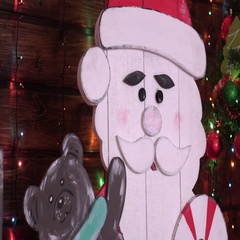 Wooden snowman of ornaments and gifts with a tree, lights background Stock Footage