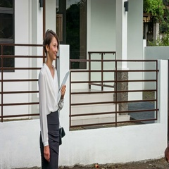 Beautiful young real estate agent meets the client near the new home. Stock Footage