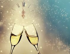 Glasses with champagne against holiday lights and clock close to midnight Stock Photos