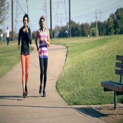 Two women jogging one pulls a muscle and sits on a bench Stock Footage