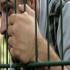 Stalker hidden behind a gate keeps an eye at his ex-girlfriend Stock Footage