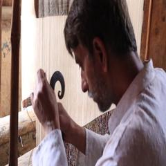 Carpet weaving. Man weaves a carpet Kashmir at weaving factory, India, Srinagar Stock Footage