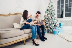 Cheerful family sitting in the living room having fun with the digital tablet Stock Photos