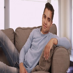 Portrait of handsome young Hispanic man sitting on couch in living room smiling Stock Footage