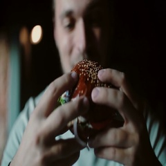 Man enjoys eating, tasting the delicious big burger meat with cheese and Stock Footage
