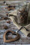 New bronze toy heart and glass jar with anise on a wooden old table. Stock Photos