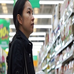 Mixed race Asian mother shopping for stuffs in baby section Stock Footage