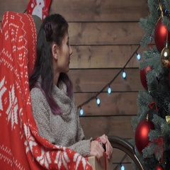 Young pretty woman on rocking chair at xmas time Stock Footage