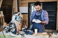 Carpenter texting someone on his smart phone near circular saw in a dusty Stock Photos