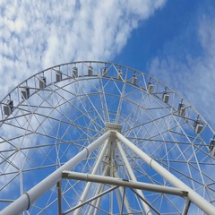 Underside view of a ferris wheel against blue sky with clouds. Stock Footage