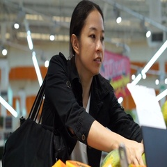 Asian immigrant woman grocery shopping for fruit the supermarket Stock Footage