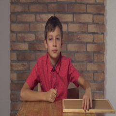Child sitting at the desk holding flipchart with lettering no on the background Stock Footage