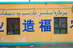 """Text on the wall in Chinese and Uyghur arabic script saying """"Blessing the journe Stock Photos"""