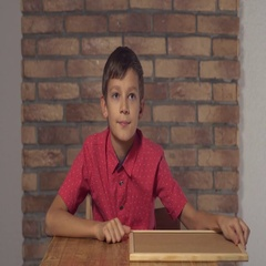 Child sitting at the desk holding flipchart with lettering yes on the background Stock Footage