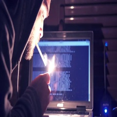 Young hacker hooded lights a cigarette while violating a computer Stock Footage