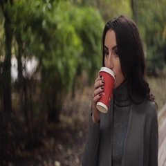 Beautiful girl drinks coffee in cold autumn park Stock Footage