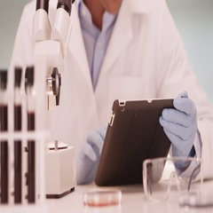 Millennial Latino medical scientist in laboratory using tablet computer Stock Footage