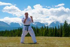 Man in white kimono and black belt training karate on mountain background Stock Photos