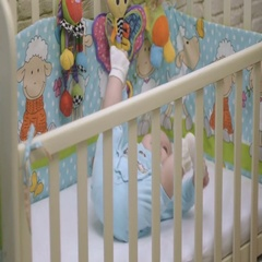 Baby is in the playpen and keeps his feet in his hands Stock Footage